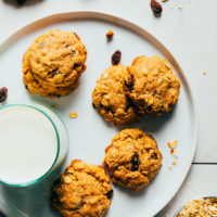Plate of vegan oatmeal cookies next to a glass of dairy-free milk