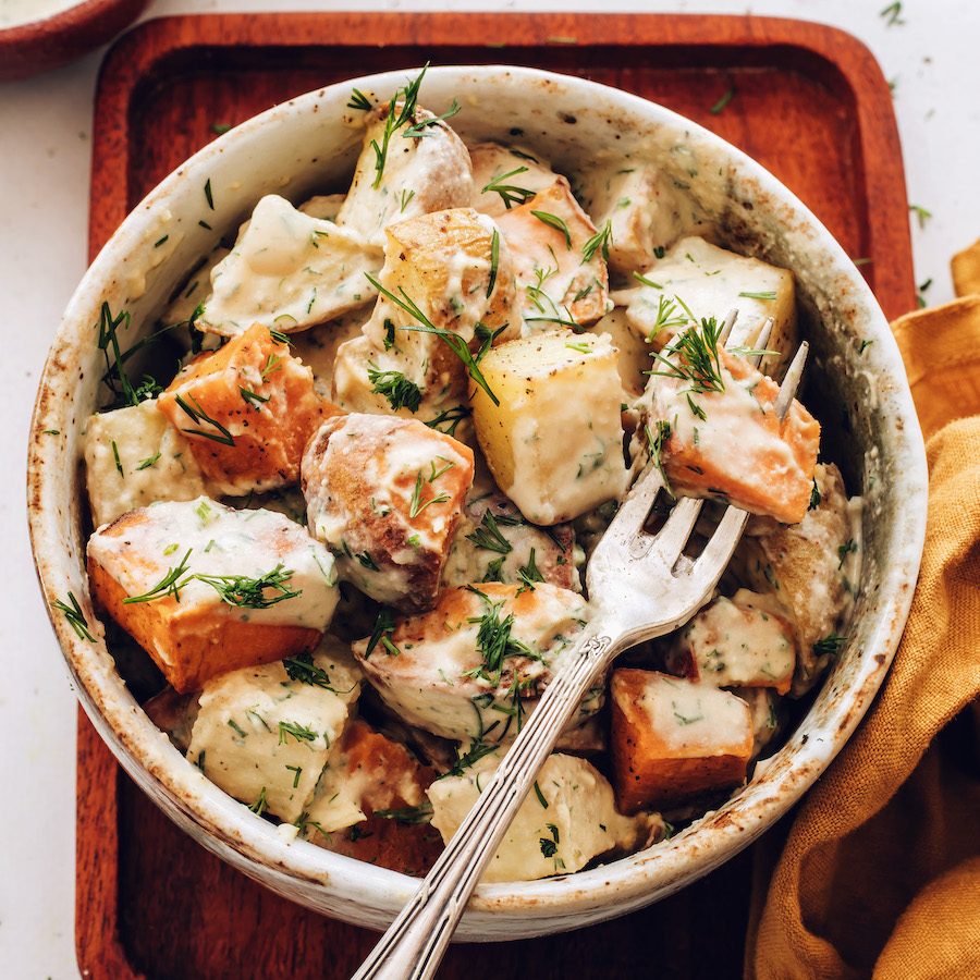 Fork spearing a potato in a bowl of our roasted potato salad recipe
