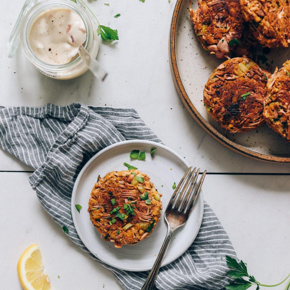 Two plates with vegan crab cakes next to a jar of vegan tartar sauce