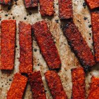 Strips of crispy vegan tempeh bacon on a baking sheet