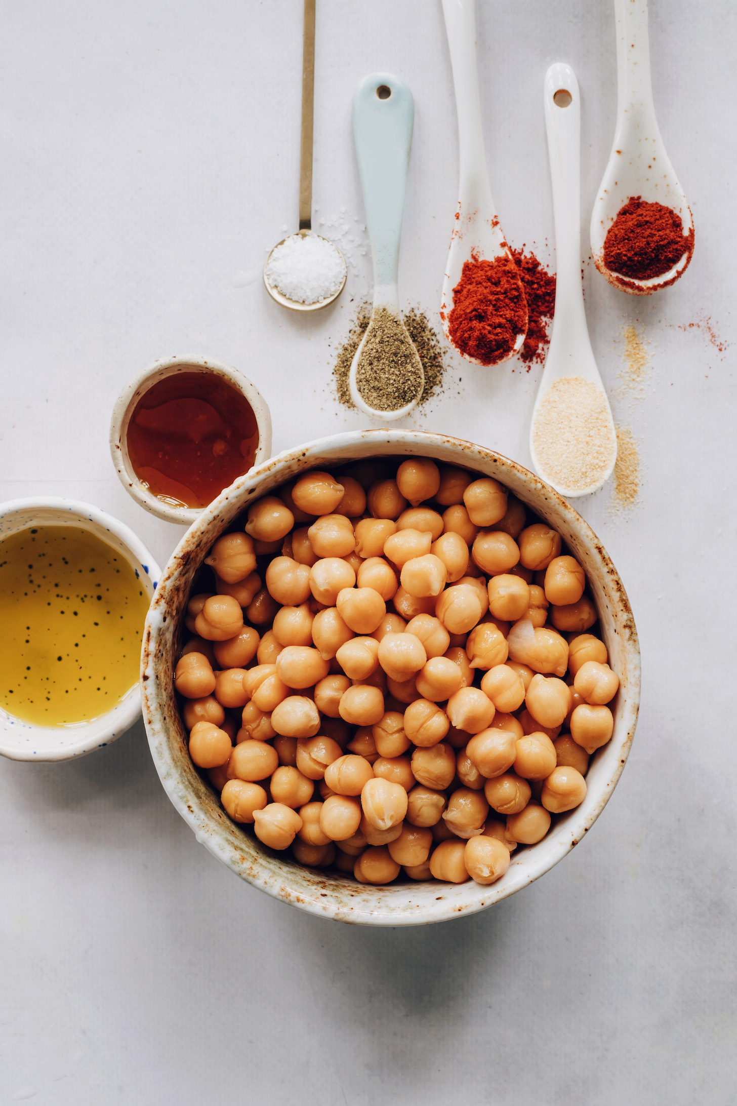 Bowl of chickpeas next to avocado oil, maple syrup, and spices