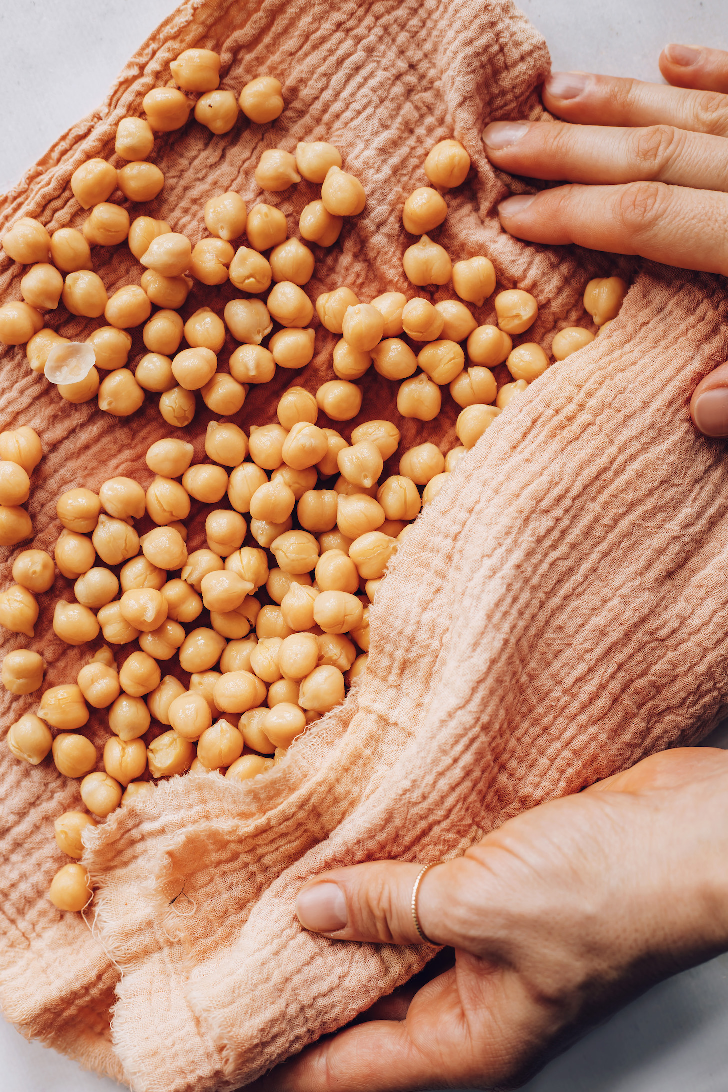 Using a kitchen towel to remove the peels from garbanzo beans
