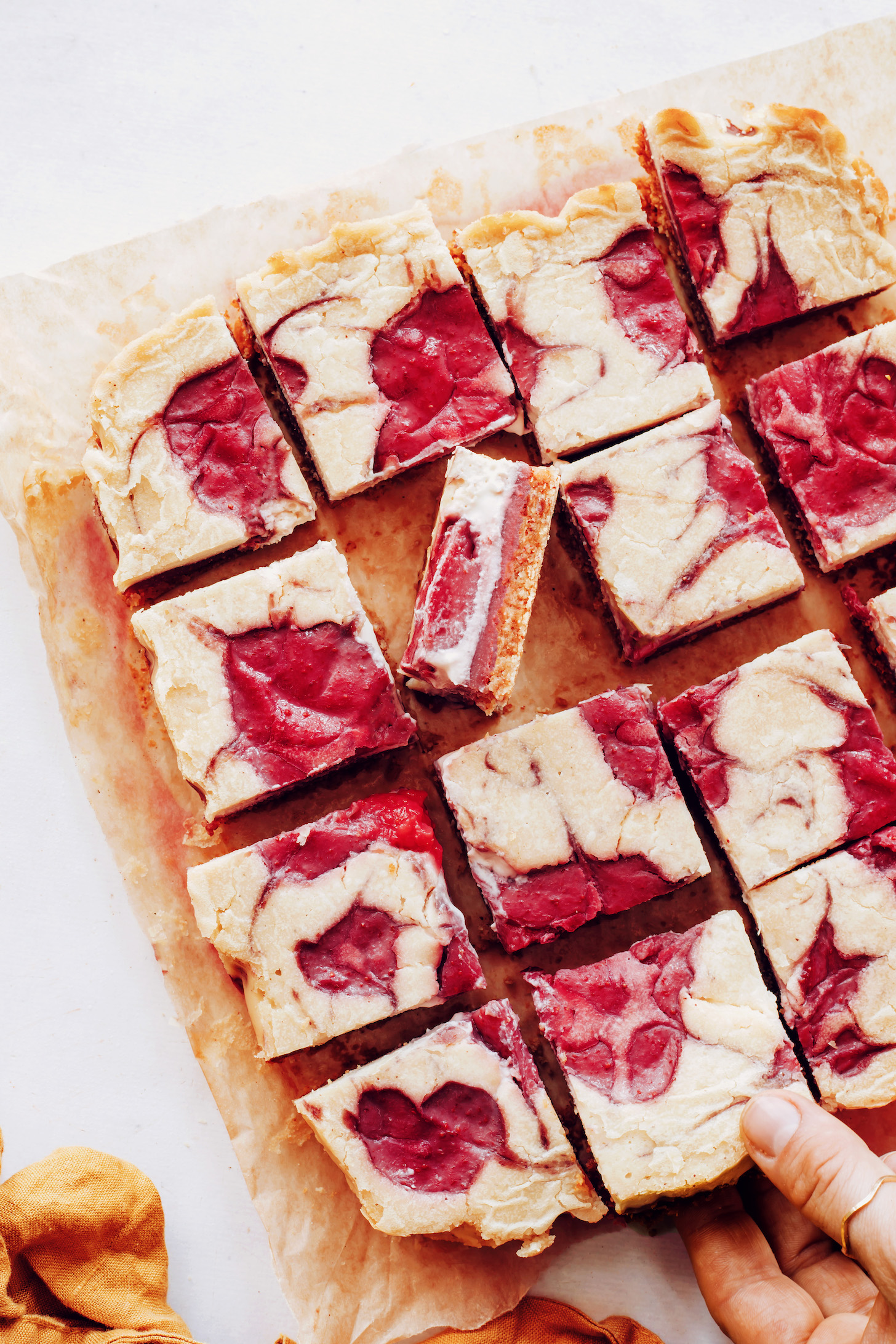 Gluten-free vegan strawberry cheesecake bars on a piece of parchment paper