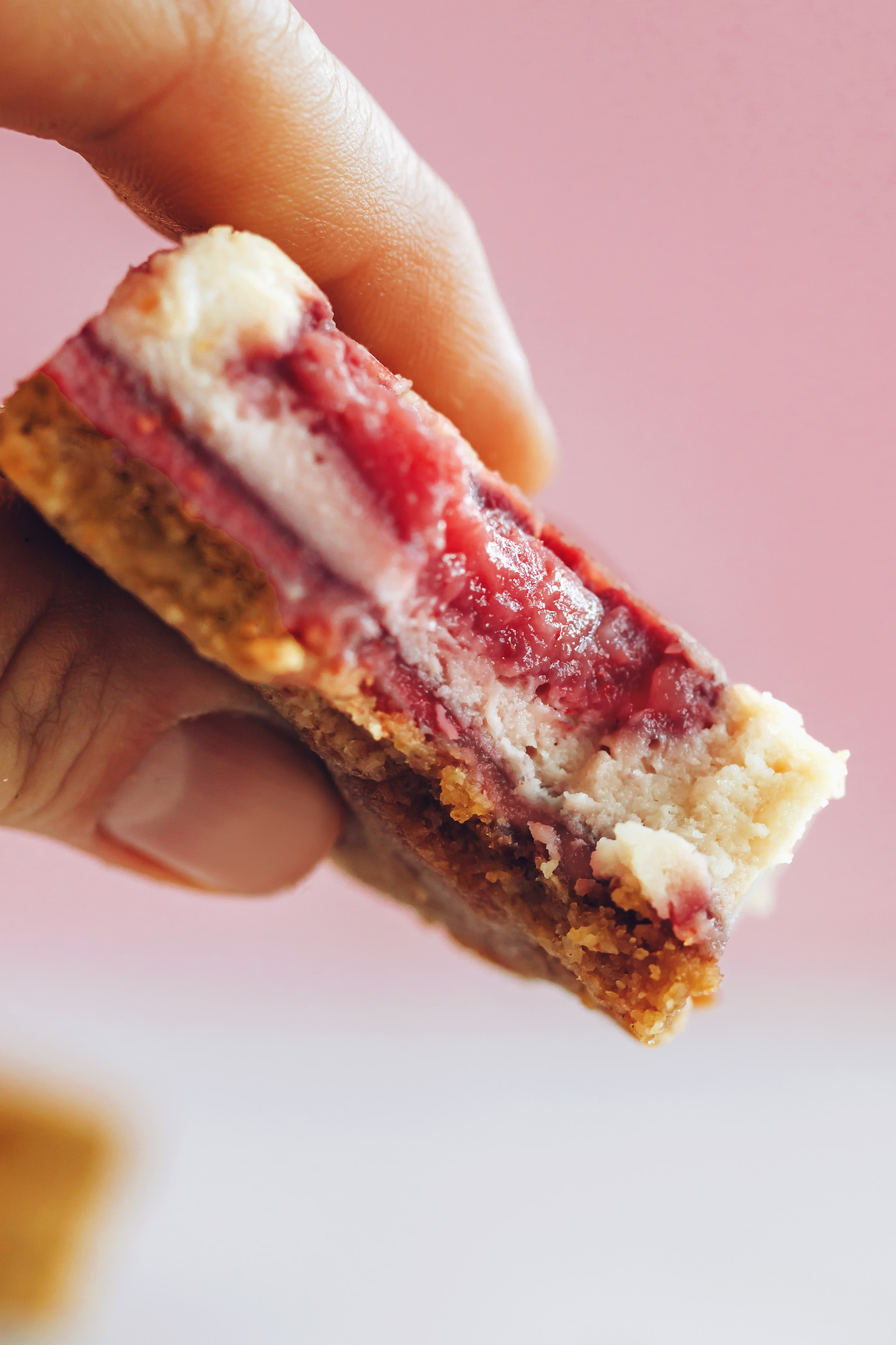 Holding up a strawberry cheesecake bar to show the texture