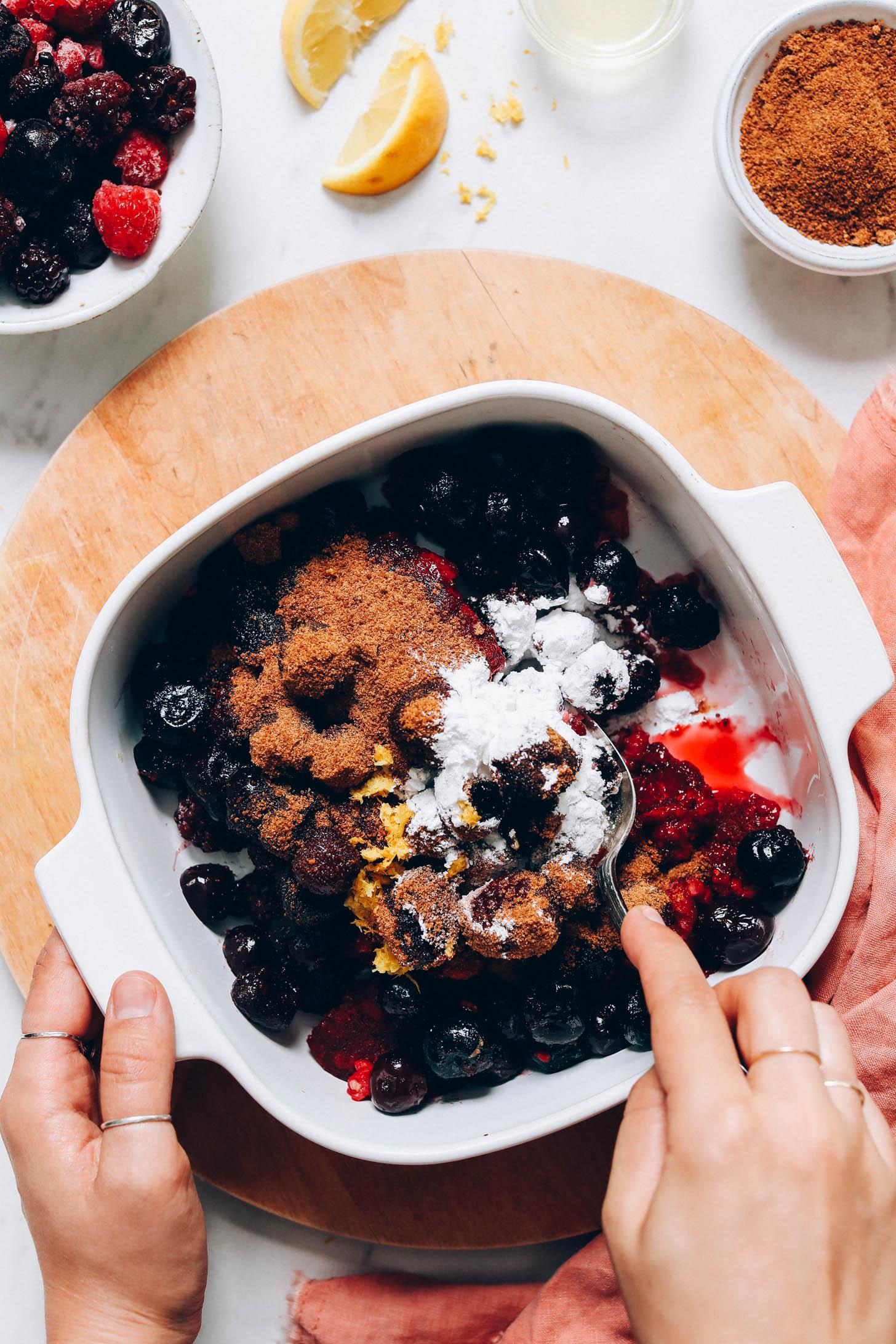 Stirring frozen berries, coconut sugar, arrowroot powder, and lemon zest