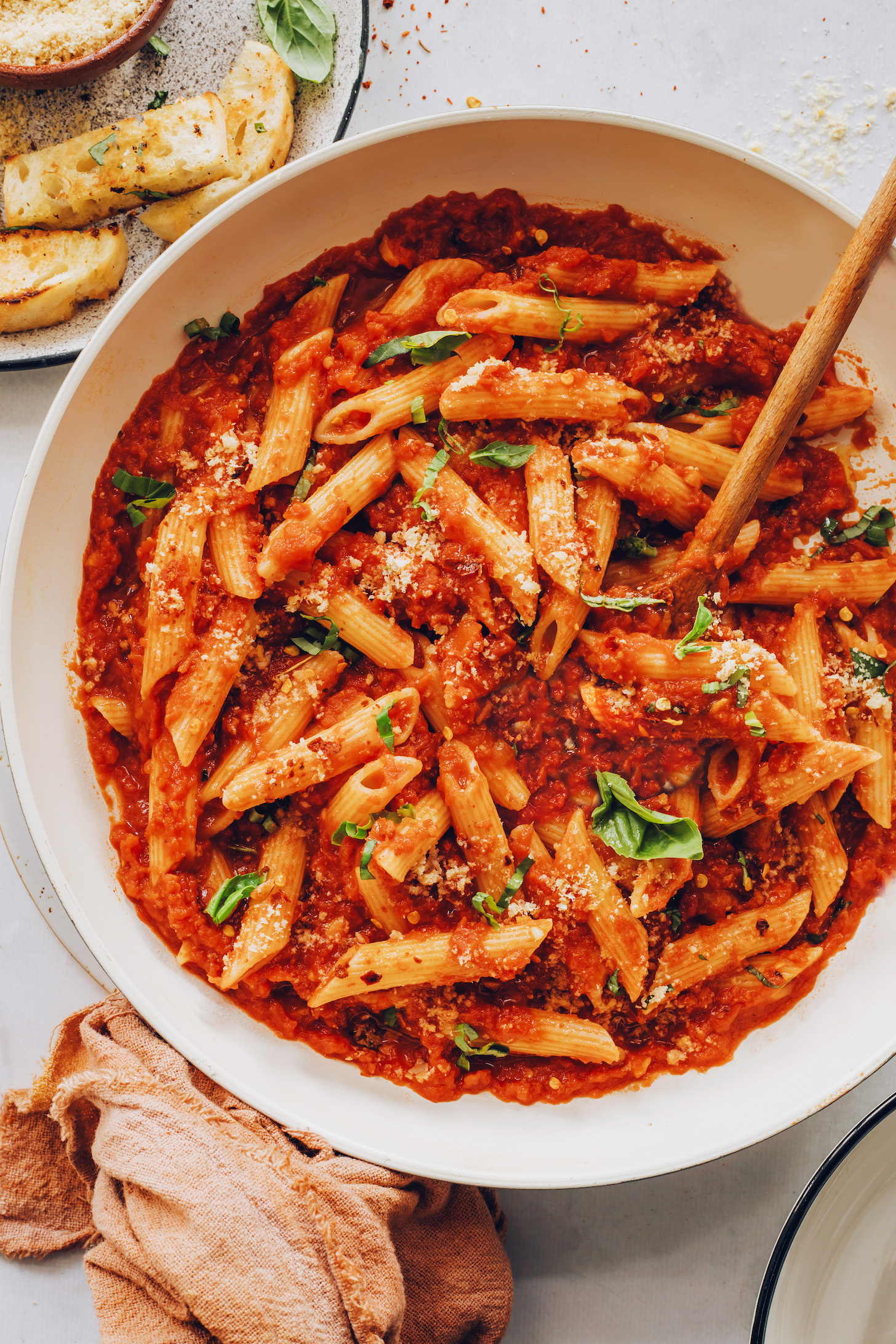 Slices of garlic bread next to a pan of our easy penne arrabbiata recipe