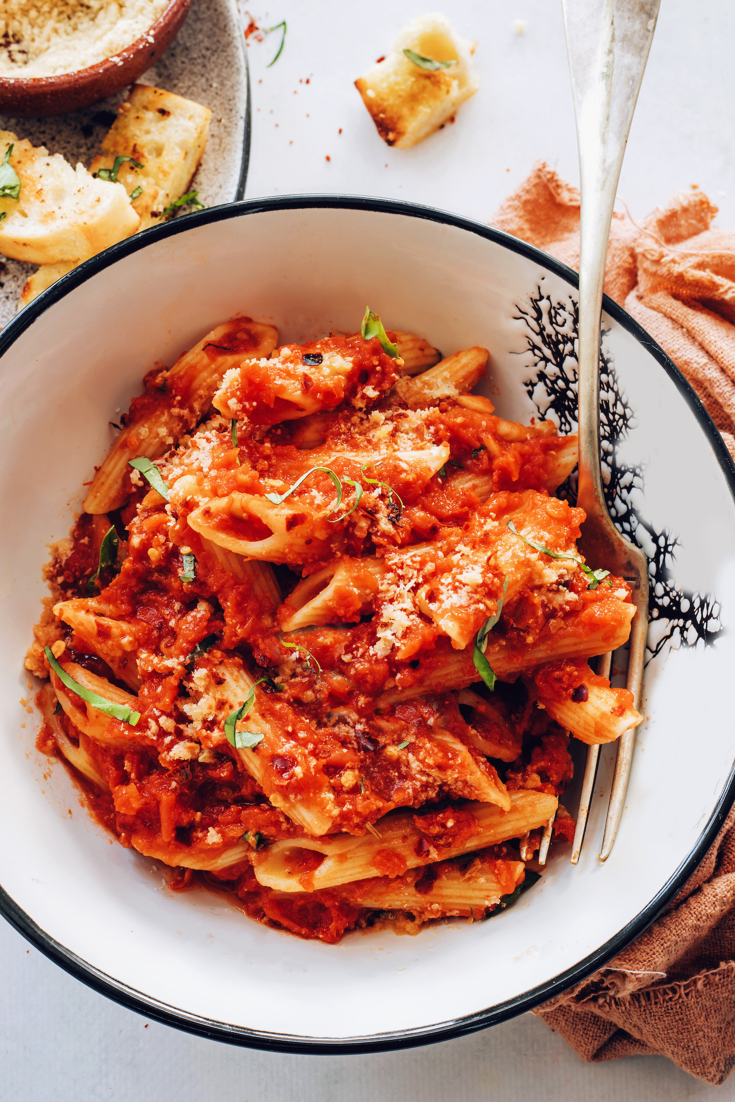 Bowl of penne arrabbiata topped with vegan parmesan cheese and fresh basil