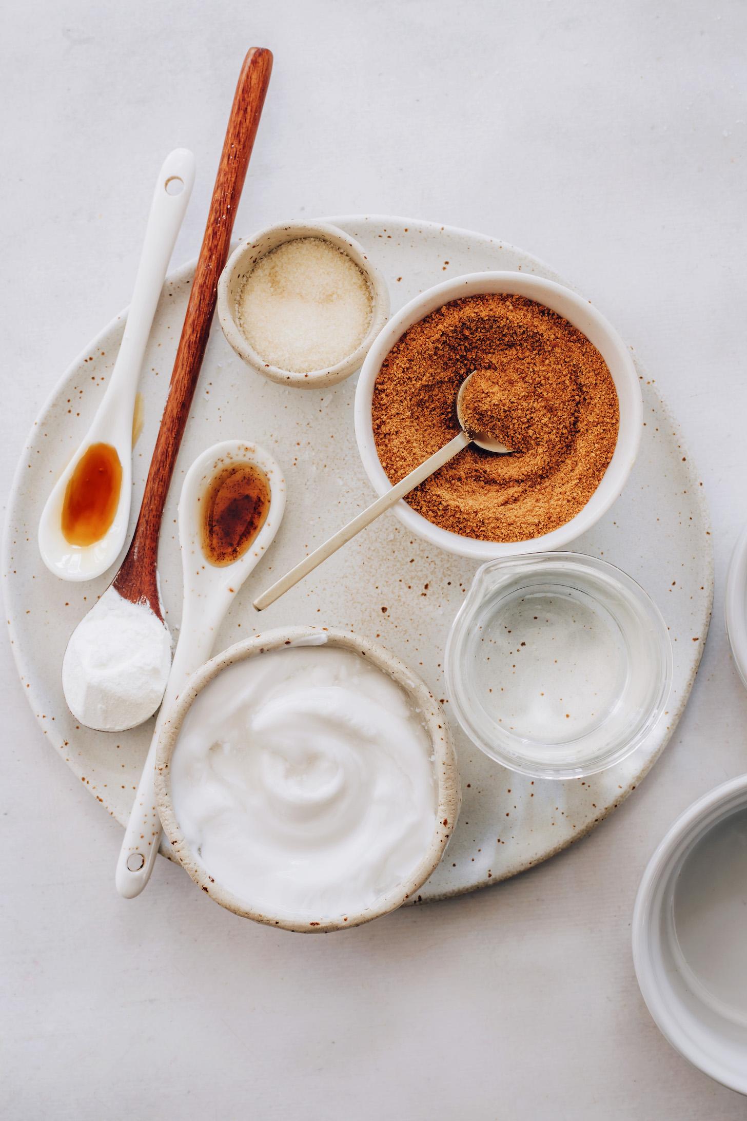 Bols et cuillères de sucre de coco, sel, vanille, fécule de maïs, sirop d'érable, lait de coco et eau