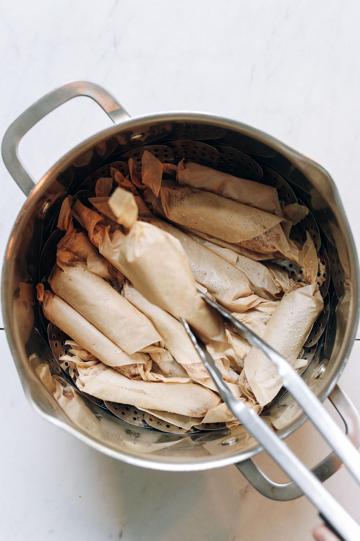 Utiliser des pinces pour retirer un lien de saucisse végétalienne pour une poêle à vapeur