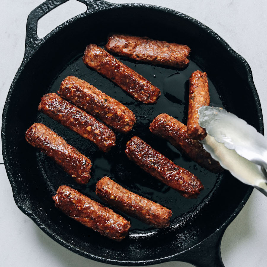 Flipping a vegan sausage link cooking in a cast iron skillet