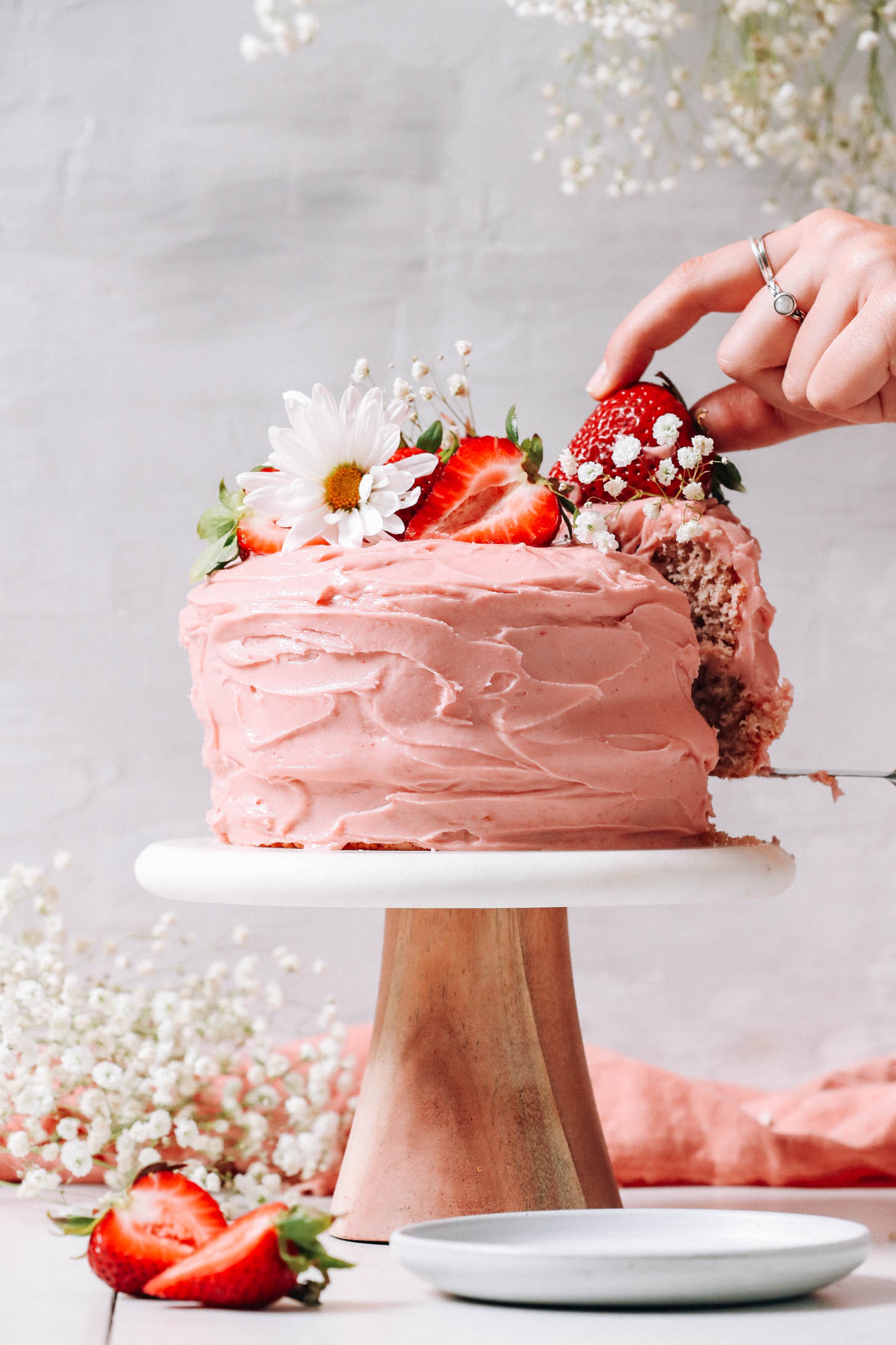 Gluten-free vegan strawberry cake decorated with fresh strawberries and flowers