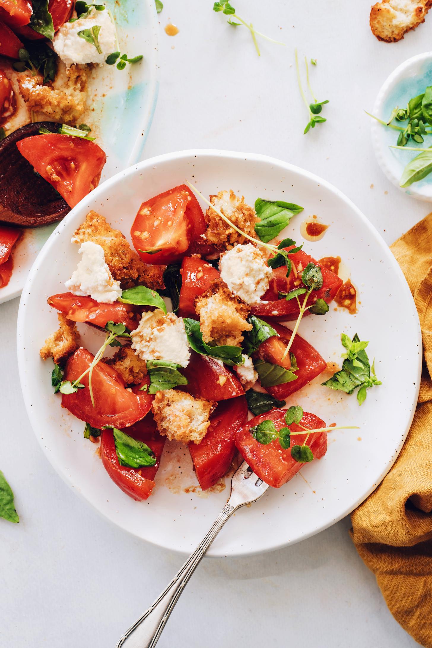 Fork in a bowl of heirloom tomato caprese panzanella salad
