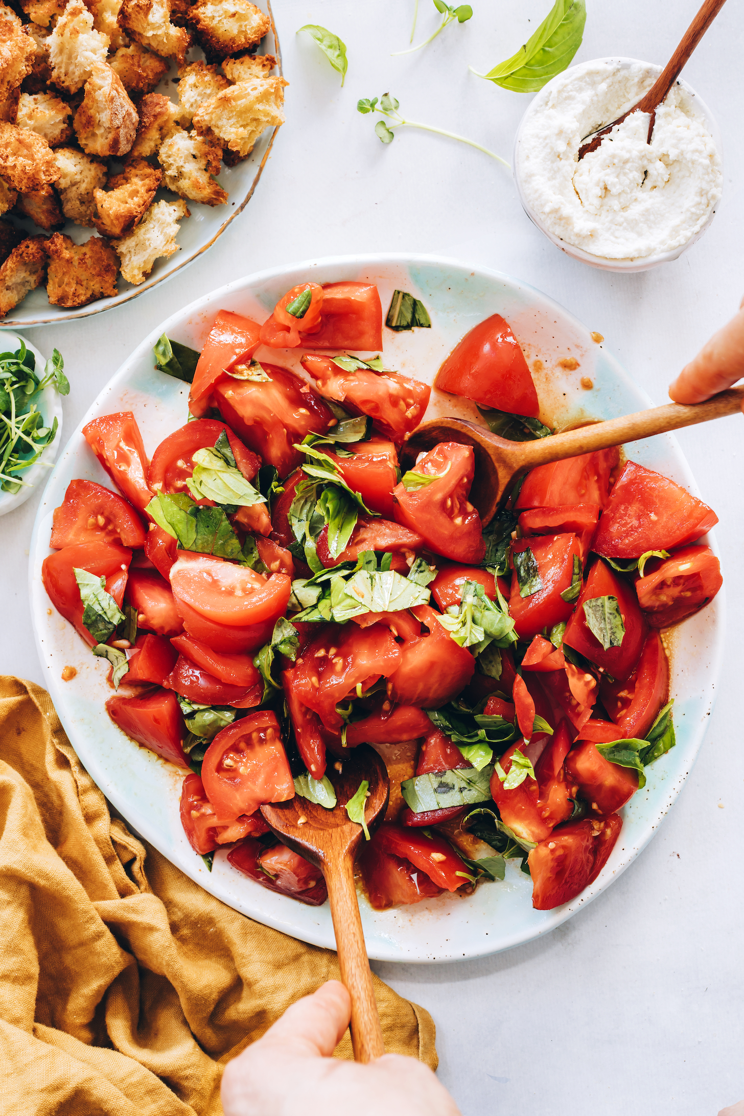 Tossing fresh tomatoes and basil with dressing