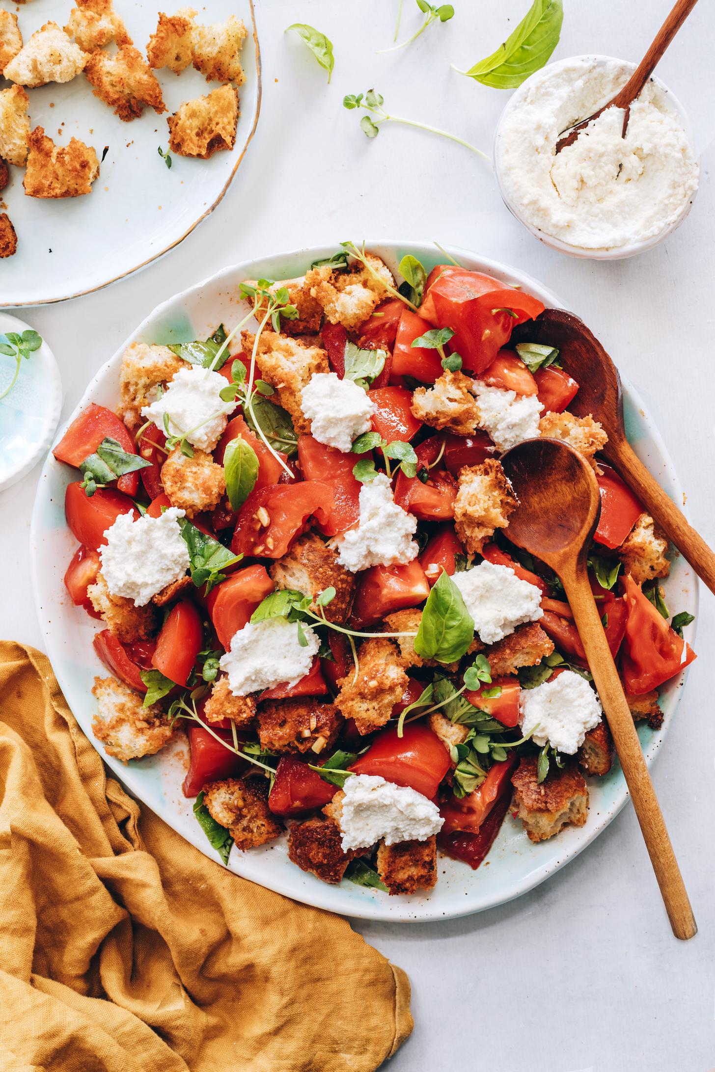 Platter of tomato panzanella salad with basil, microgreens, and cashew ricotta