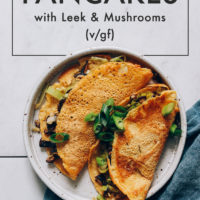 Plate of savory chickpea pancakes folded with leeks and mushrooms