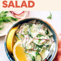 Bowl of vegan and gluten-free creamy cucumber salad with fresh lemon wedges, dill, and radishes on the side