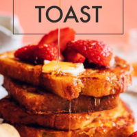 A stack of easy vegan french toast with raspberries, maple syrup, and vegan butter