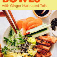 A vegan sushi bowl with fresh chopped veggies, marinated tofu, and tamari on the side with chopsticks