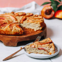 Slice and platter of millet breakfast cake with stone fruit