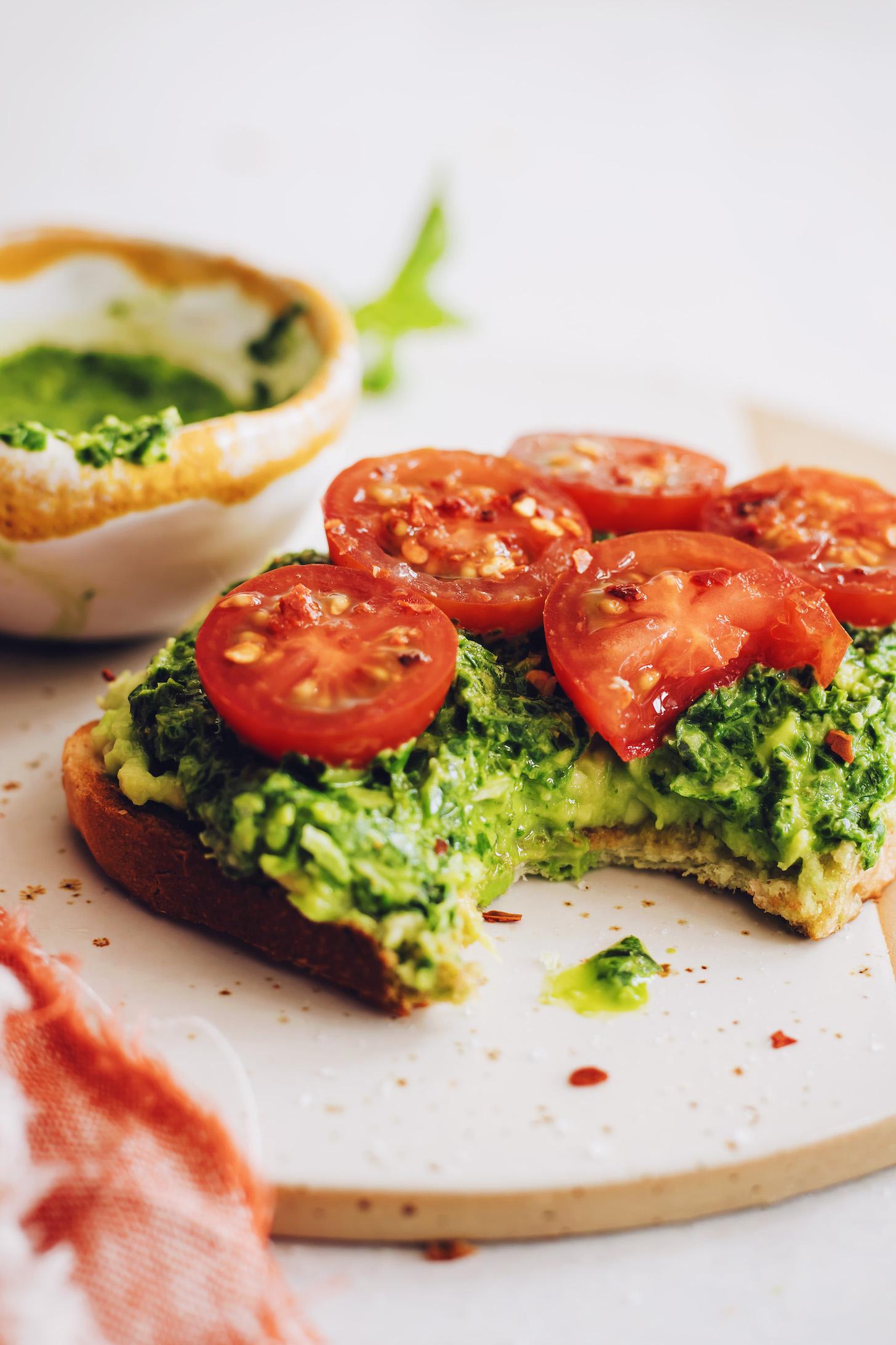 Taze domatesli bir dilim pesto avokado tostundan yenen ısırık