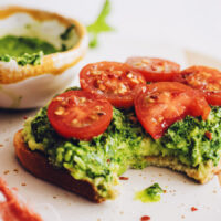 Slice of pesto avocado toast with fresh tomatoes