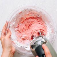 Spreading vegan strawberry frosting on a cake