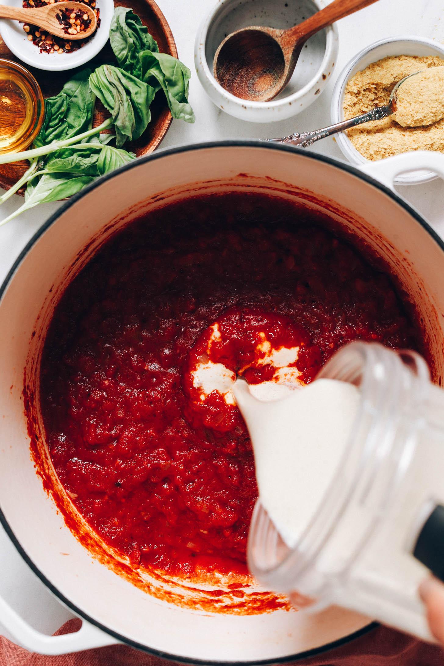 Verser la crème de cajou d'un mélangeur dans une casserole de sauce tomate