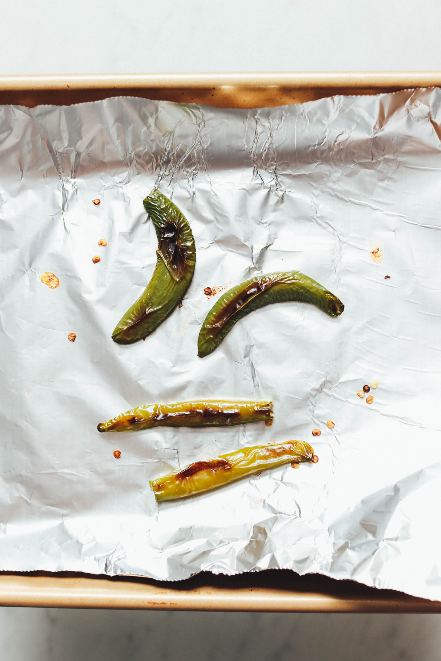 Roasted serrano peppers on a foil-lined baking sheet