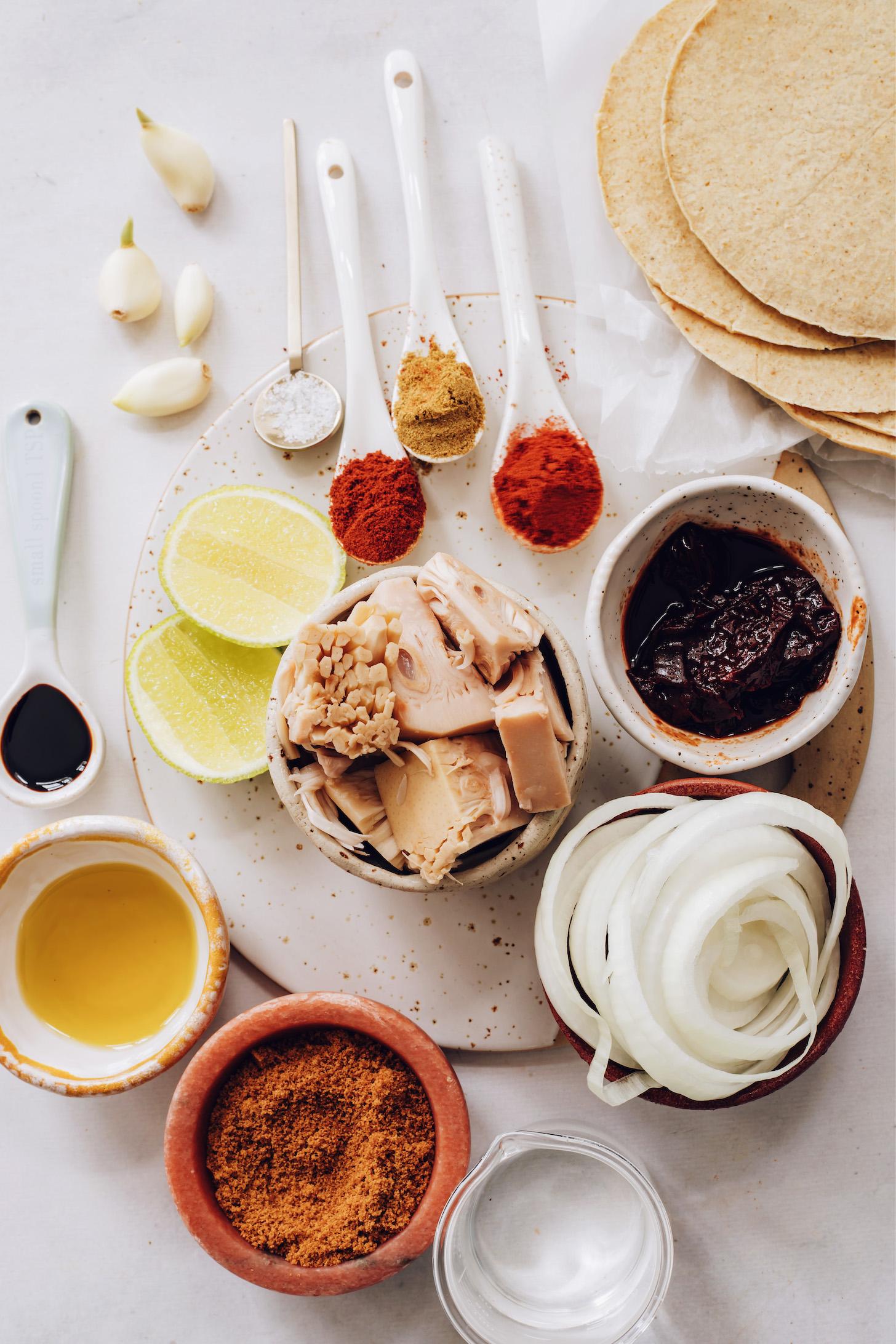 Garlic, salt, lime, spices, jackfruit, adobo pepper, onion, corn tortillas, water, oil, and coconut aminos