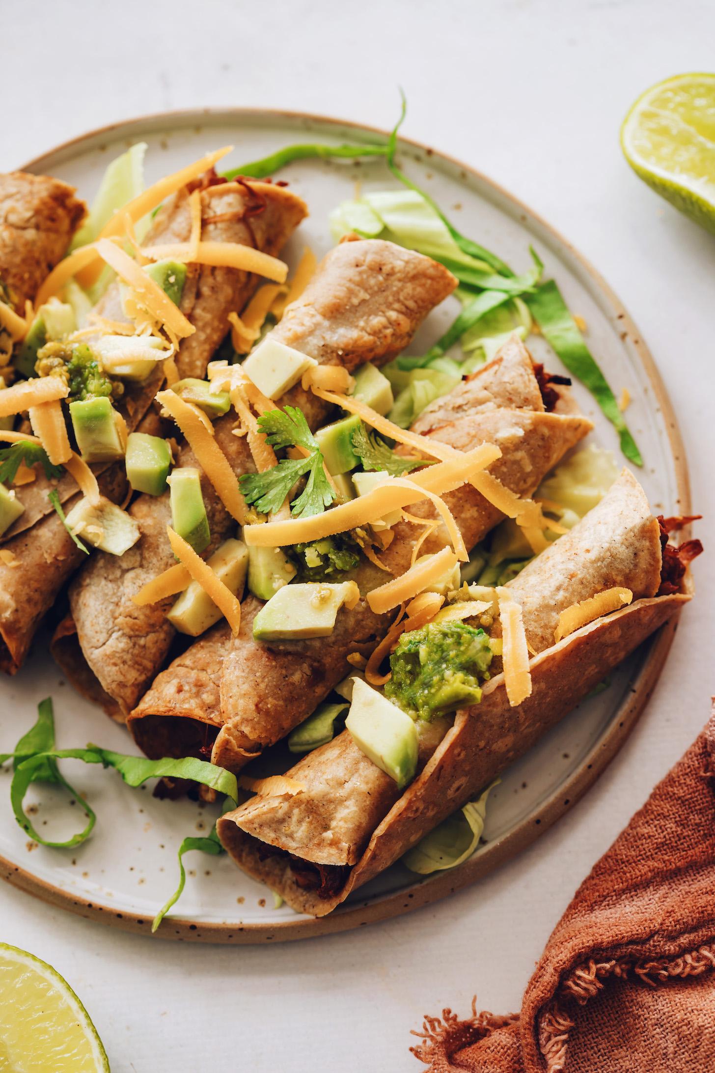 Plate of jackfruit taquitos with avocado, cilantro, lettuce, vegan cheddar, and tomatillo salsa
