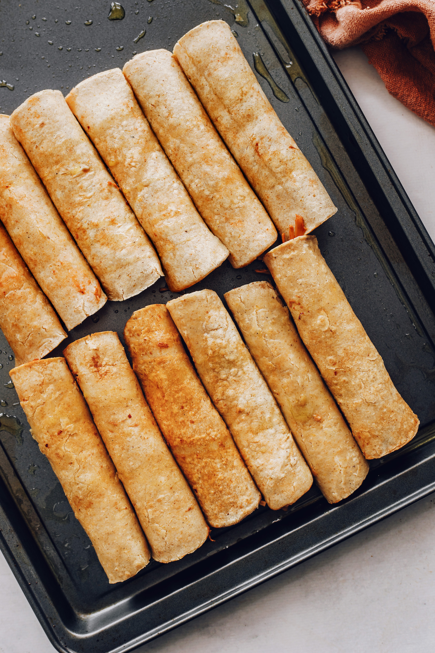 Vegan taquitos on a baking sheet ready to go in the oven