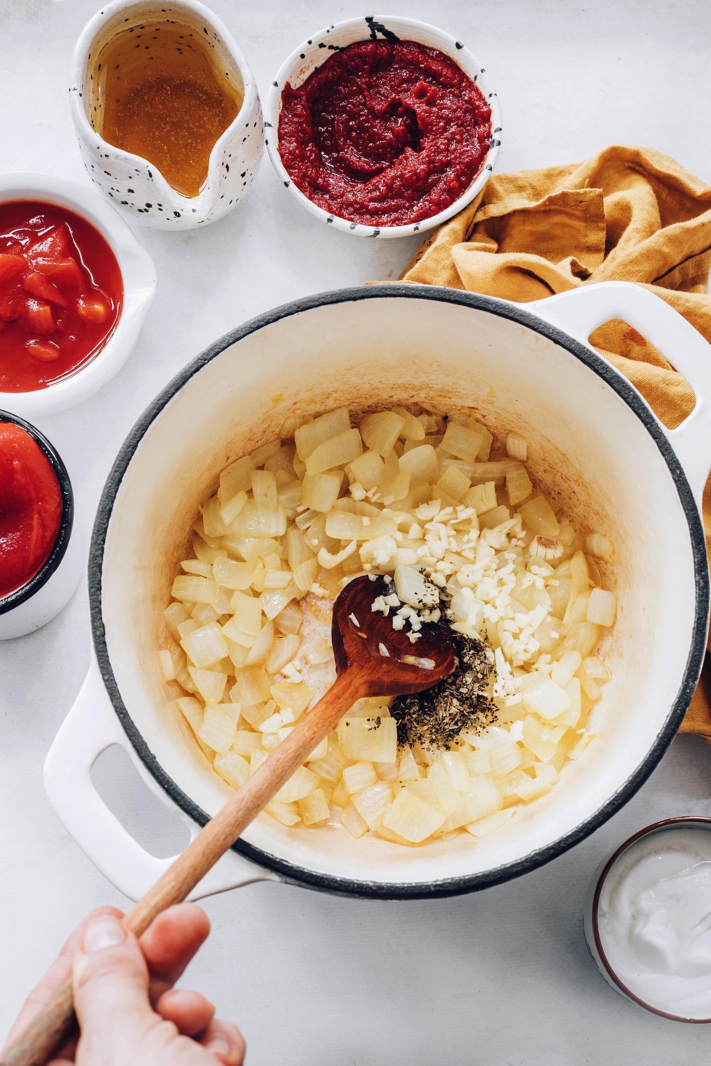 Domates, salça ve sebze suyunun yanında bir tencerede sotelenmiş soğan ve sarımsak