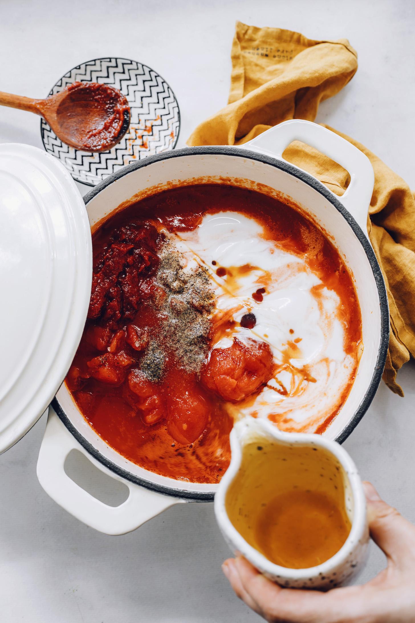 Domates, hindistan cevizi sütü, tuz, biber, fesleğen, soğan, sarımsak, akçaağaç şurubu ve et suyu içeren bir tencereye sebze suyunu dökün.