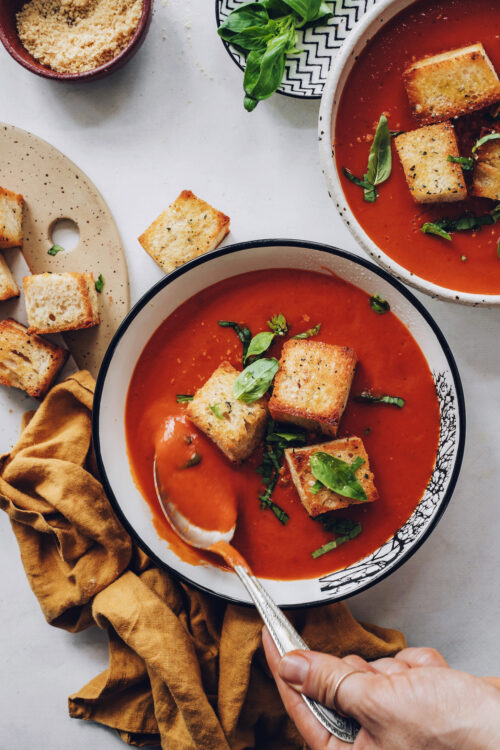 Spoon in a bowl of creamy tomato soup