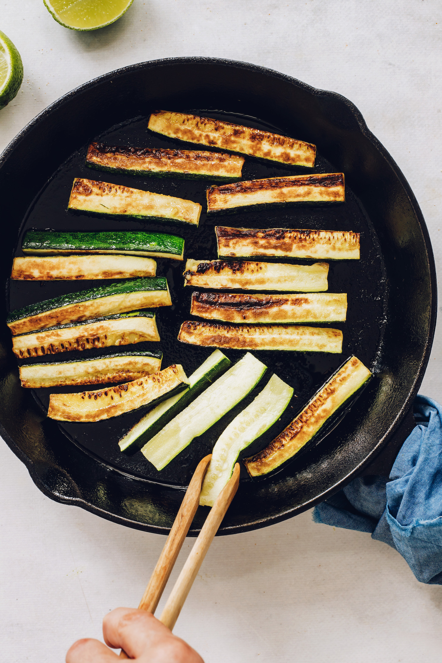 Cooking zucchini slices in a cast iron skillet