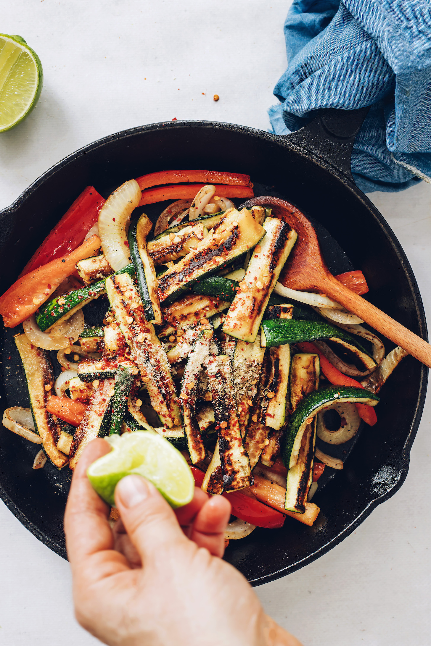 Squeezing lime into a skillet of sautéed onion, zucchini, bell pepper, and spices
