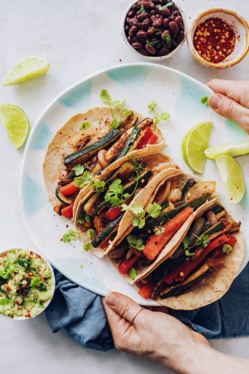 Hands holding a platter of vegan tacos with zucchini and bell pepper