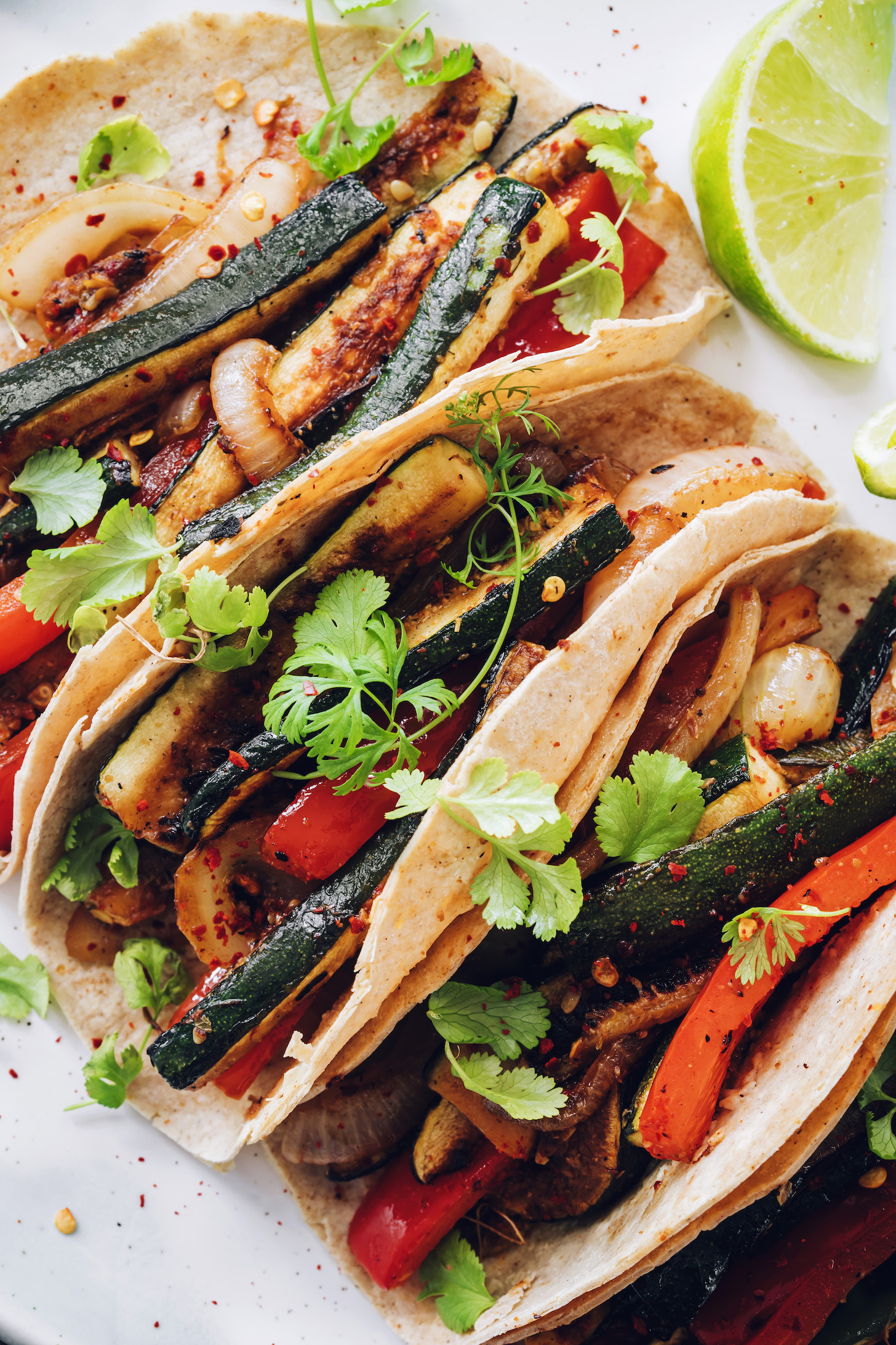 Close up shot of three vegan tacos made with zucchini, bell pepper, and onion