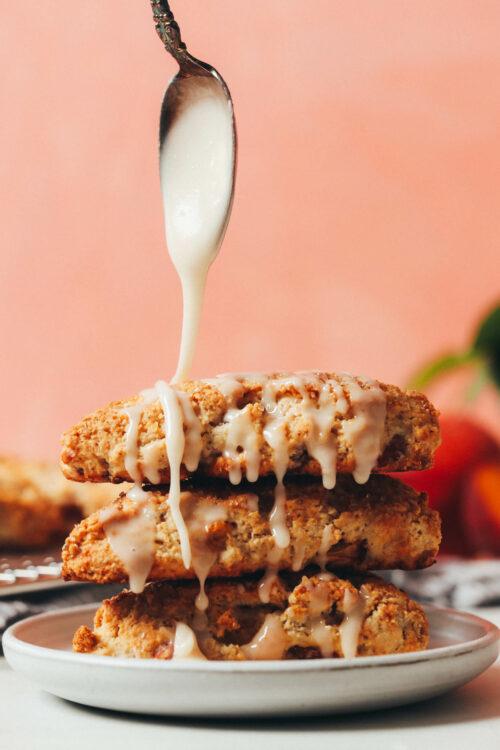 Drizzling vanilla glaze over a stack of peach scones