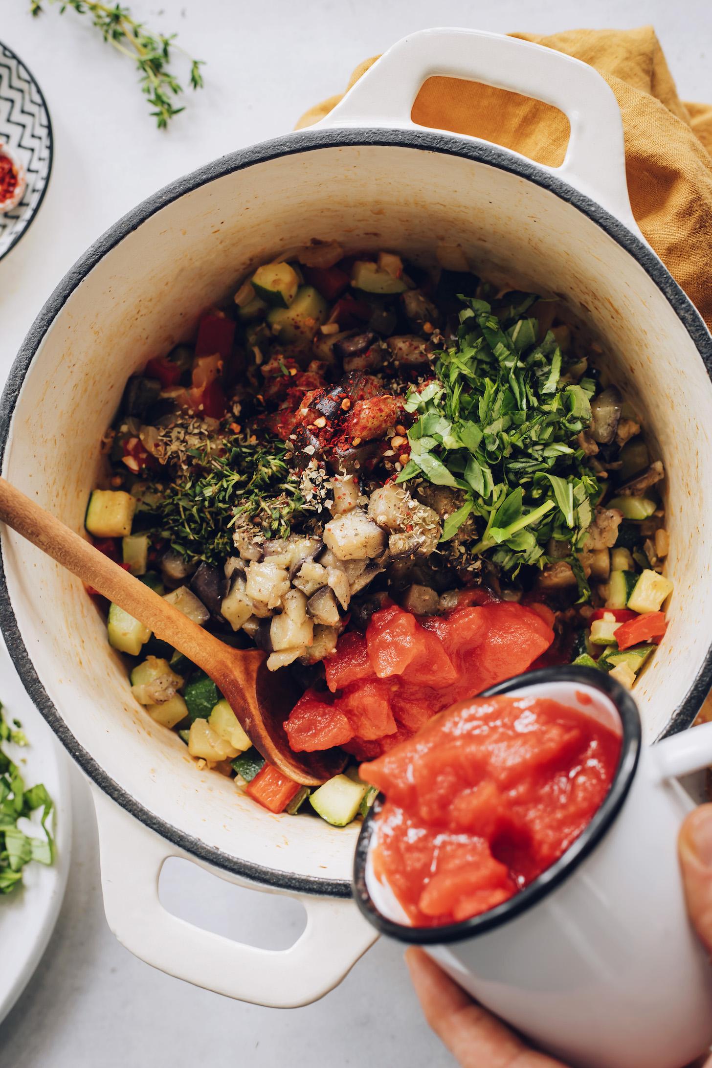 Taze otlar ile sote patlıcan, kabak ve dolmalık biber üzerine konserve domates dökme