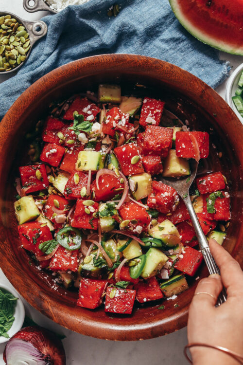 Vintage spoon in a bowl of watermelon salad with fresh cucumber and mint