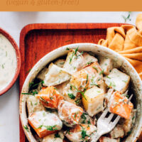 Bowl of easy vegan roasted potato salad with garlic dill dressing with a fork in it