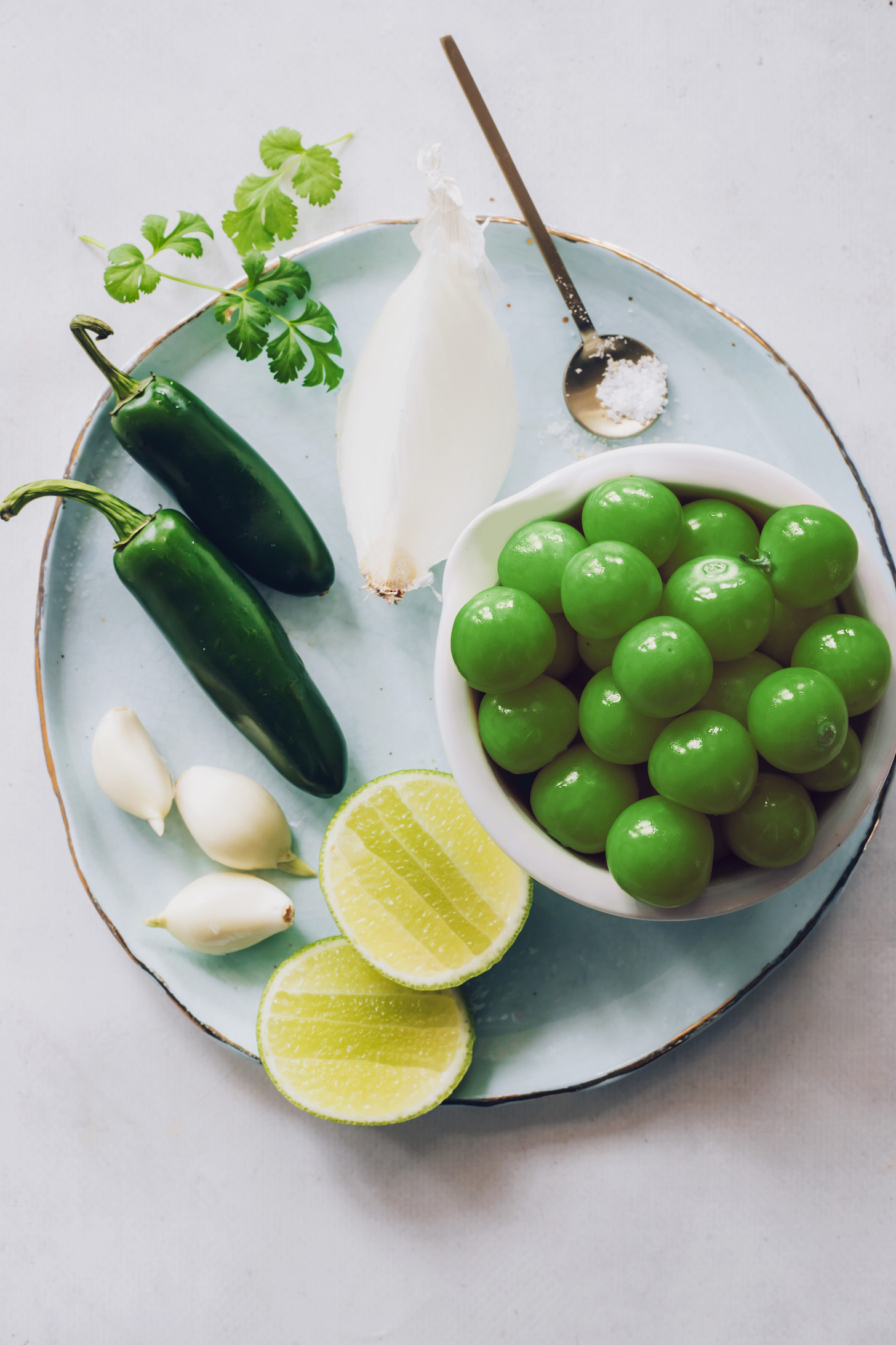 Tomatillos, onion, salt, limes, garlic, jalapeño, and cilantro
