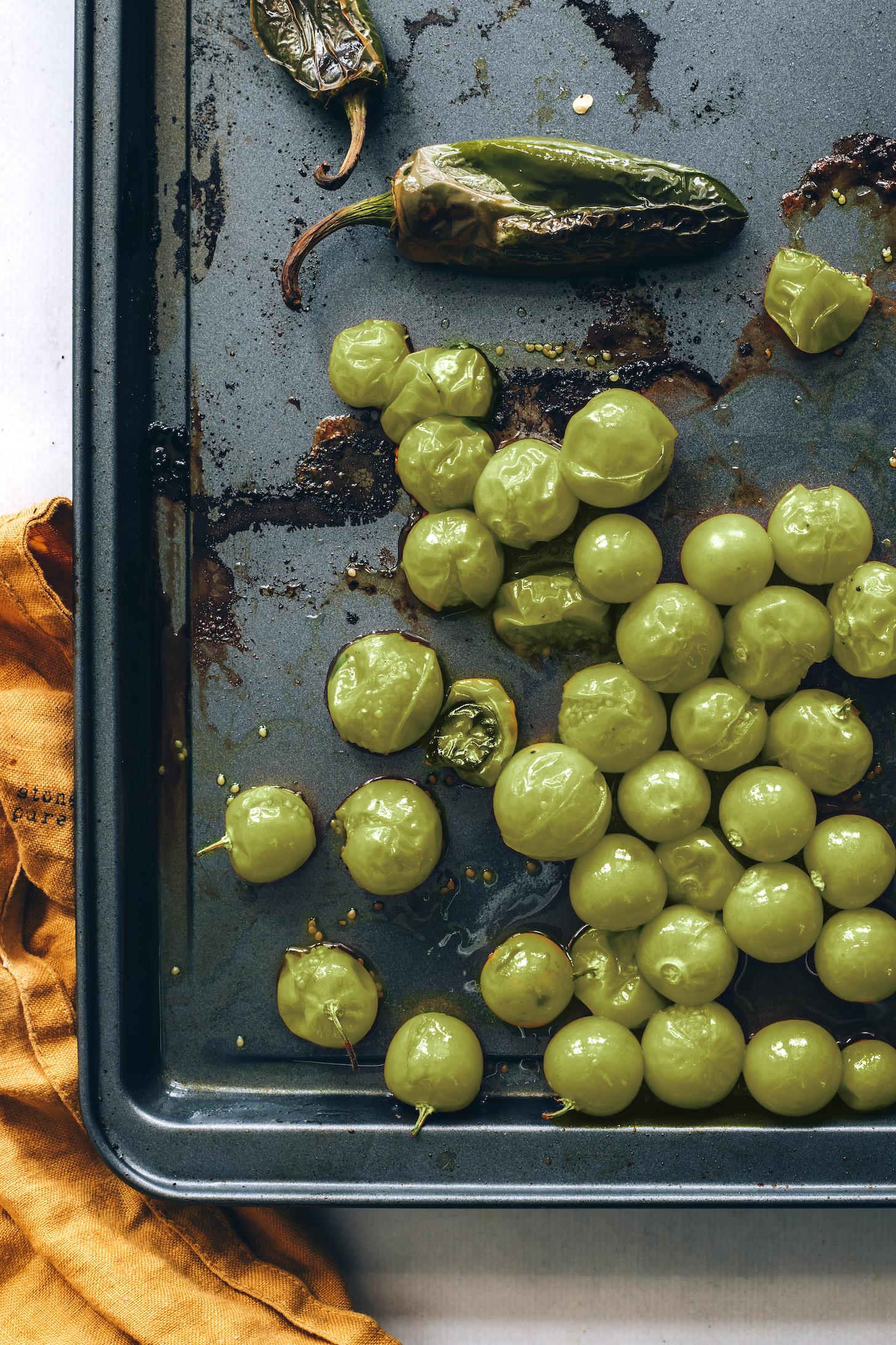 Roasted jalapeños and tomatillos on a baking sheet