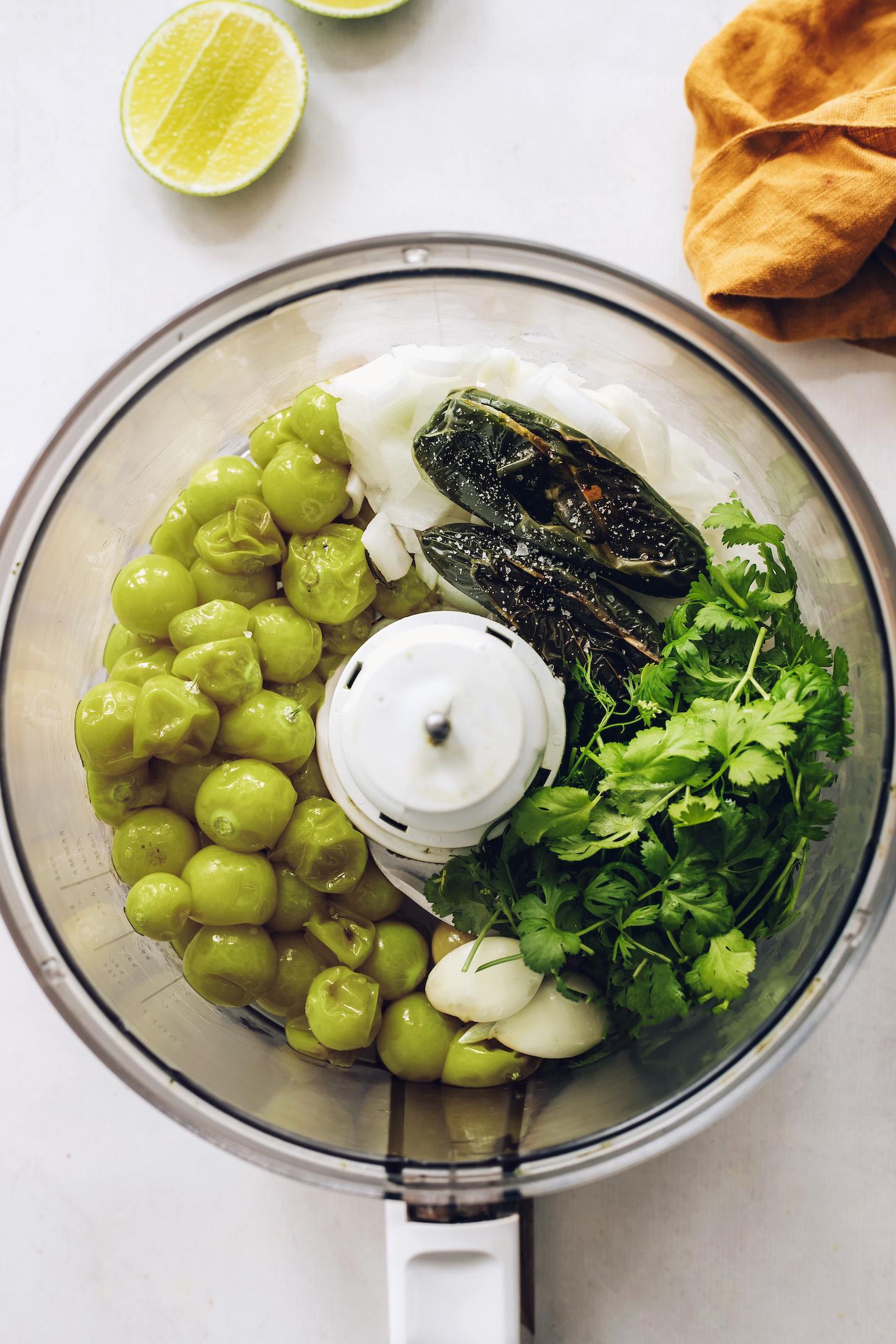 Food processor with roasted tomatillos and jalapeños, cilantro, garlic, onion, and salt
