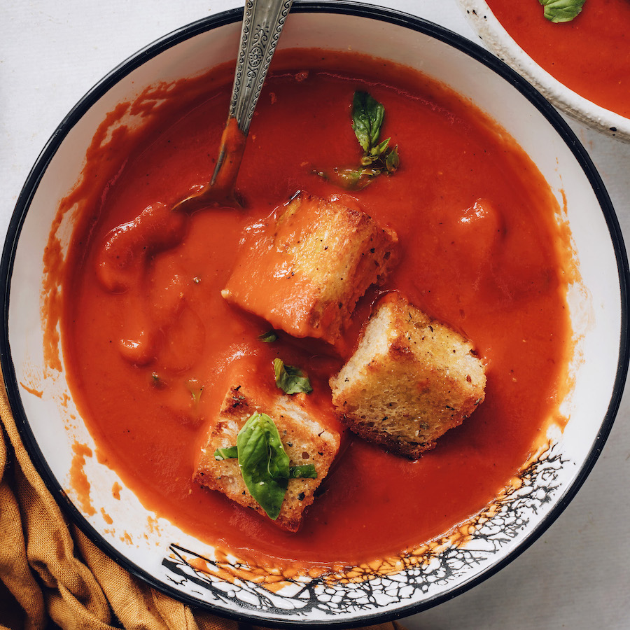 Bowl of creamy vegan tomato soup topped with croutons