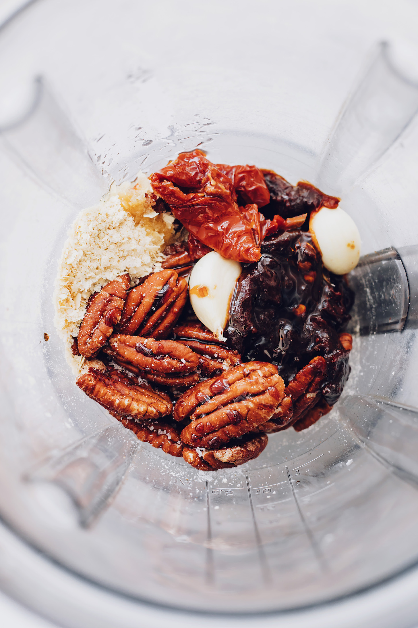 Blender with pecans, garlic, sun-dried tomatoes, salt, chipotle peppers, and nutritional yeast
