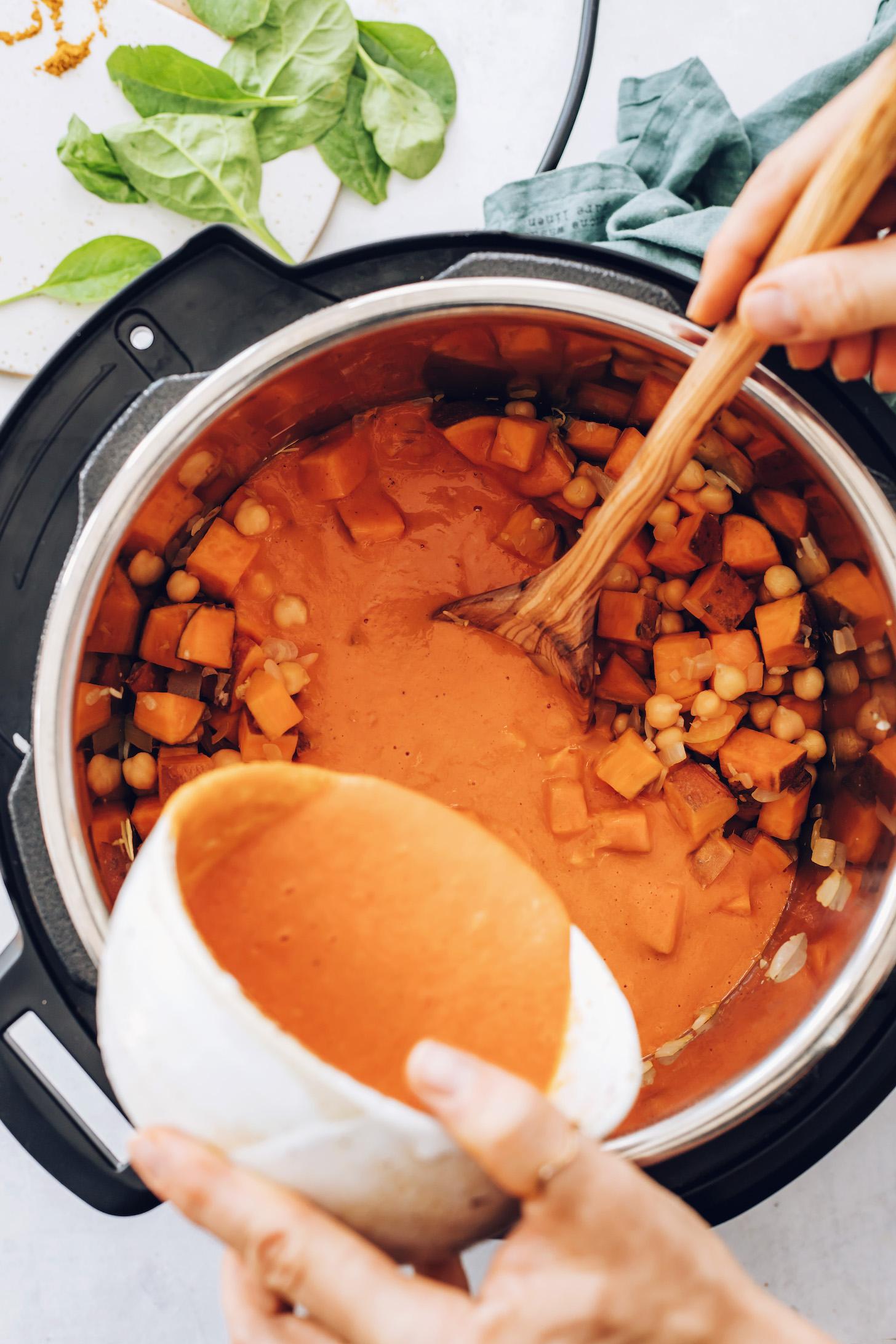 Sotelenmiş soğan, sarımsak, zencefil, tatlı patates ve nohutların üzerine közlenmiş kırmızı biber sosu dökün