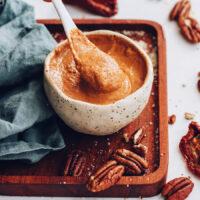 Spoon in a bowl of creamy chipotle pecan pesto