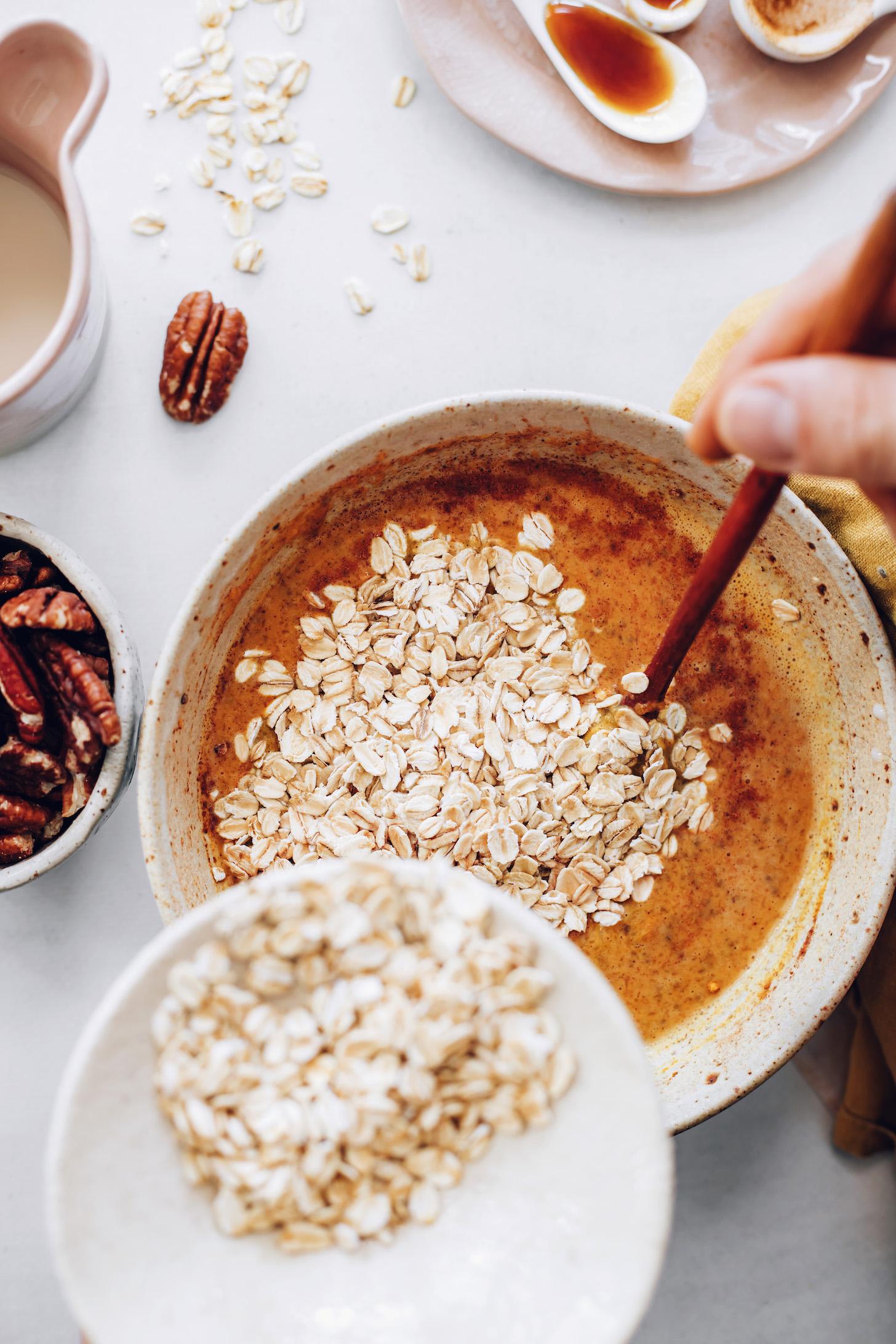 Verser les flocons d'avoine dans un bol de purée de citrouille, de lait d'amande et d'autres ingrédients humides